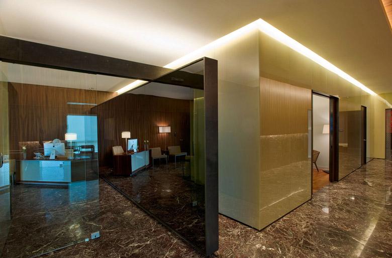 这是一家从事购物中心项目开发的集团公司总部设计,设计意在通过设计语言、环境氛围、空间构造来创建一个摩登时尚的办公空间,并营造出温馨如家的舒适氛围。  设计师通过熟练的材料搭配,将大理石、木材两种不同质地的自然材质混搭在一起,形成强烈的反差与对比,并配以钢化玻璃、不锈钢、铁等材料元素,形成丰富的色彩与材质对比,由此构建一个时尚温馨的办公环境  电梯厅采用卡拉拉白大理石,美丽的自然肌理营造出时尚冷艳的气质,墙面局部运用黑色金属,与大理石形成强烈的视觉反差,暖色的壁灯柔化了空间。进入接待区却是一个完全不同的温暖